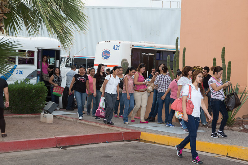 Manufacturing Employees in Guaymas Mexico getting off of the bus