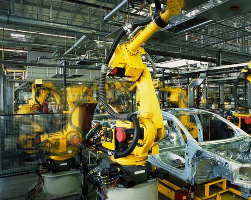 A large yellow robotic arm works to create the shell of a car.
