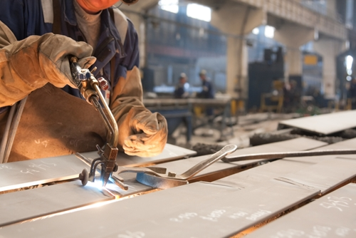 A picture of an employee in a factory welding a large piece of metal.