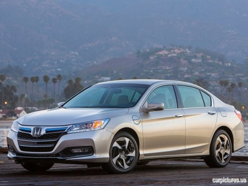 A new honda vehicle stands on a hill overlooking other green hills.