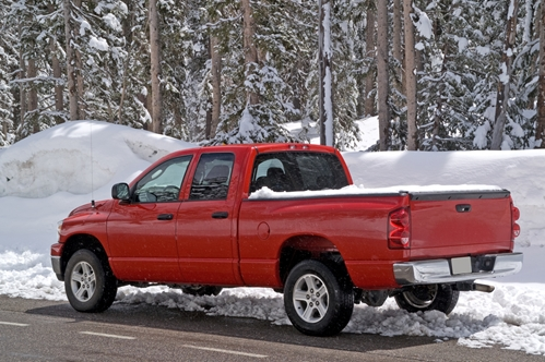 A large red truck in a forest covered with snow.