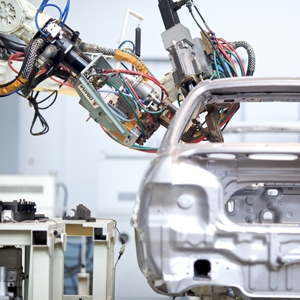 There is a robotic arm working to manufacture part of the shell of an automobile.