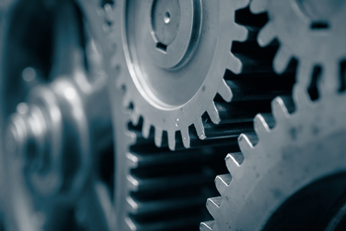 There are several large grey gears working together to create a manufacturing machine.