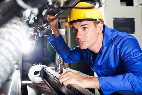 A male employee looking deeply into the mechanisms within factory machinery.