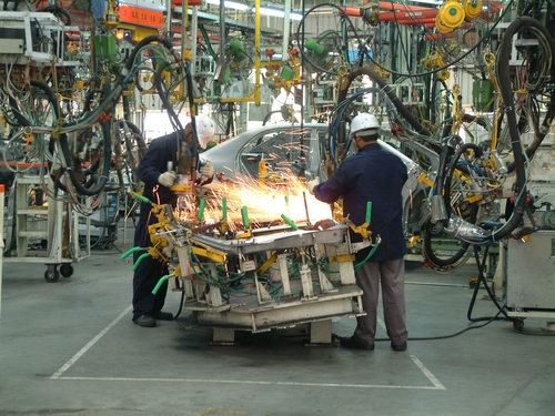 Skilled workers work to assemble an automotive vehicle.