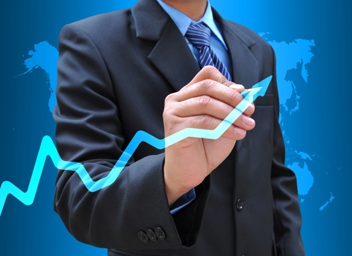 A man drawing an arrow that is meant to mimic the changing trends in an economy or a market.
