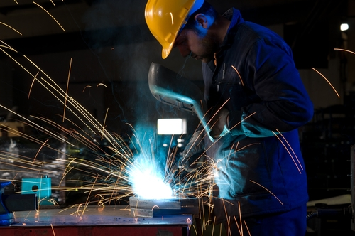 An employee works to cut a large piece of metal with sophisticated tools.