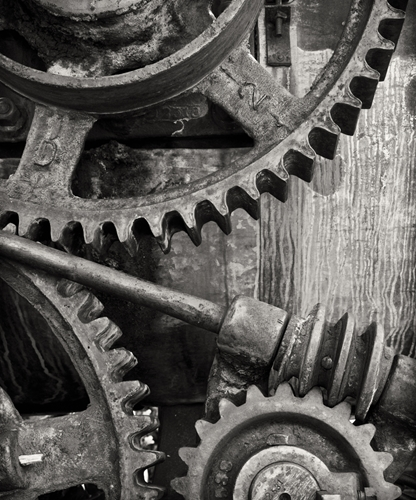 A view at oversized gray gears turning together to manufacture something.