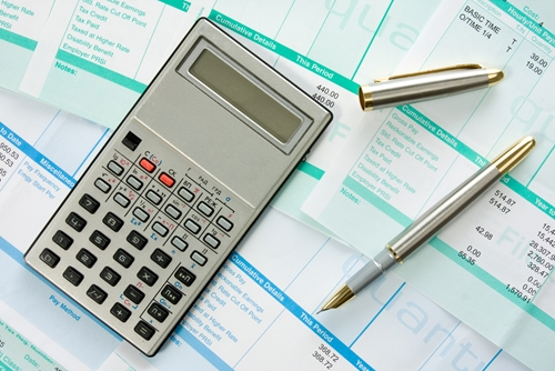 A desk with several accounting ledgers as well as a calculator and a pen.