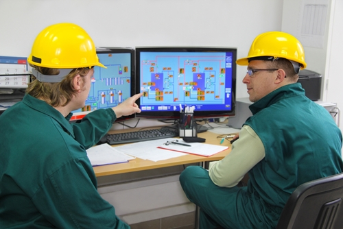 Two employees work to understand the analytics of their plant in order to improve.