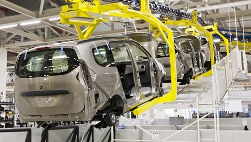 A series of robotic arms take the frame of a minivan from one end of a manufacturing facility to another.