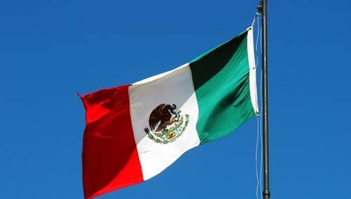 A picture of the Mexican flag waving in the blue Mexican sky.