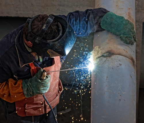 There is a man working to weld a new manufactured metal product.
