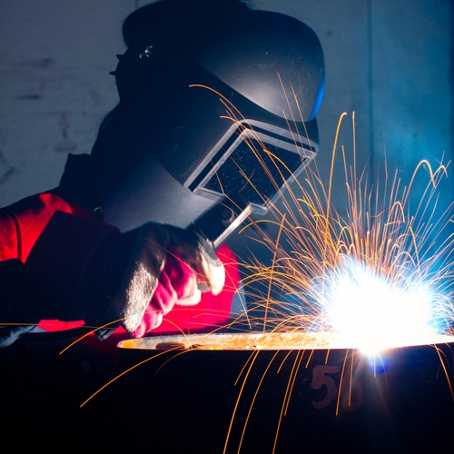 There is a picture of an employee welding a large piece of steel.