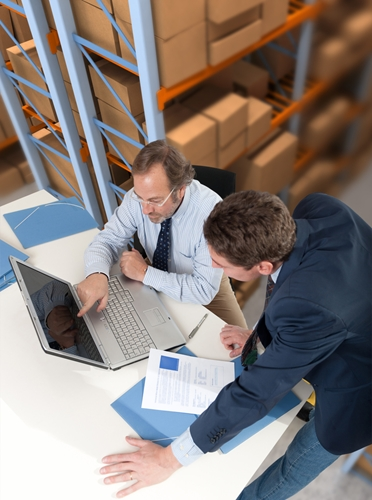 A picture of two executives discussing work issues inside a large warehouse.