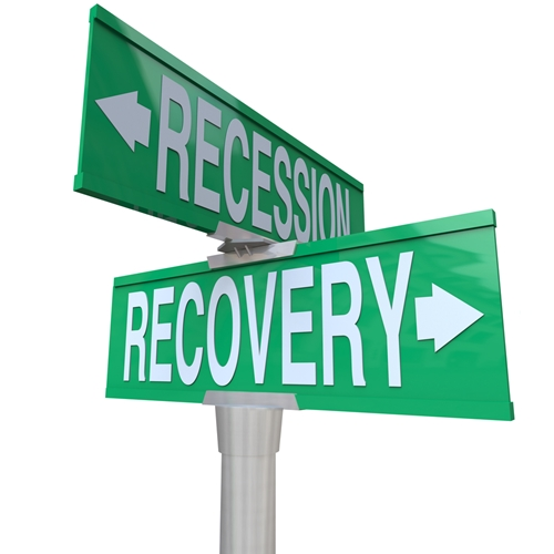 There are two street signs that read recession and recovery.