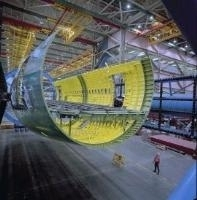 There is a picture of the inside of a manufacturing facility where there is the shell of a new airplane being built.