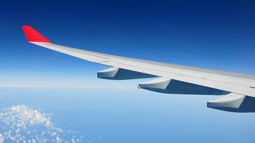 A picture of the wing of a plane flying in the clear blue skies.