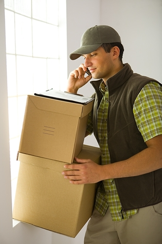 A man works to transport two large boxes from one place to another while talking on the phone.