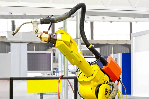 An automated robotic arm works to assemble various new products in a factory in Mexico.